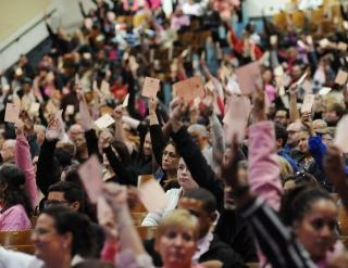 UFT delegates vote with cards in the air.