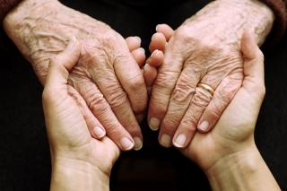 Elderly hands being held by younger hands - generic