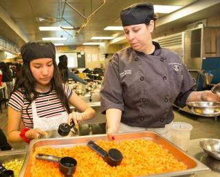 Culinary arts instructor Alexis DeVito works with a student in the kitchen.
