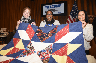 Three women holding up quilt