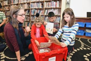 Third-grade teacher Katherine Sorel helps students choose which biography to rea