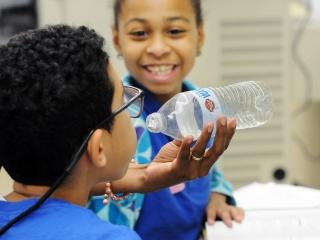 Sixth-graders test out their theory of air pressure.