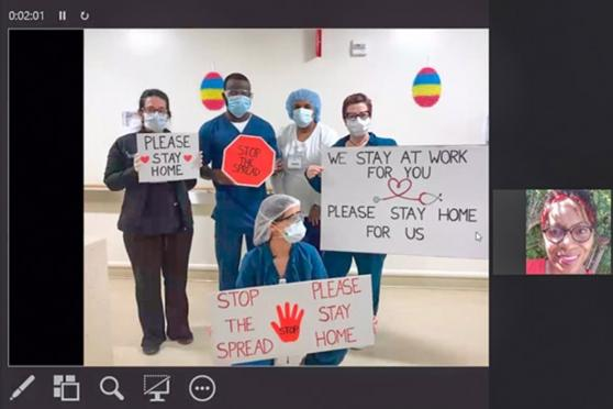 Nurses attend a video call while posing and holding up signs