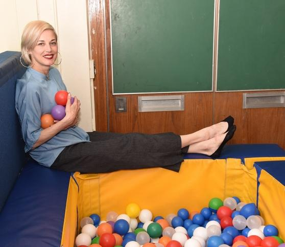 A woman sits by a small ball pit.