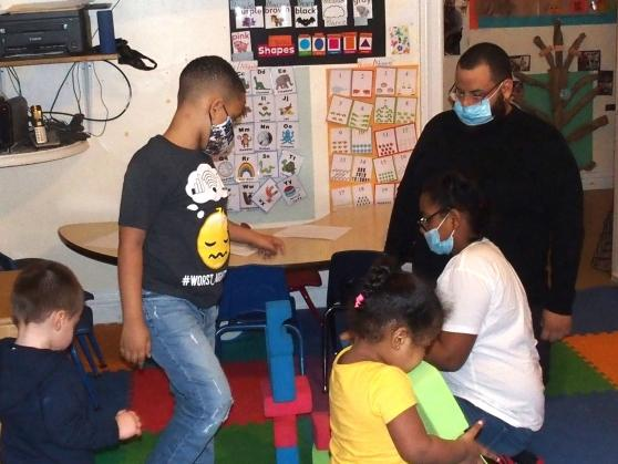 Students interact with a child care provider at a day care