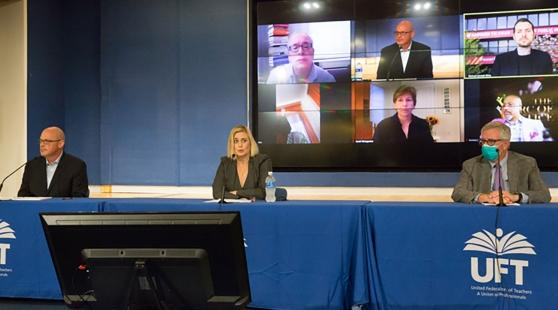 Three UFT officials speaking at a press conference podium