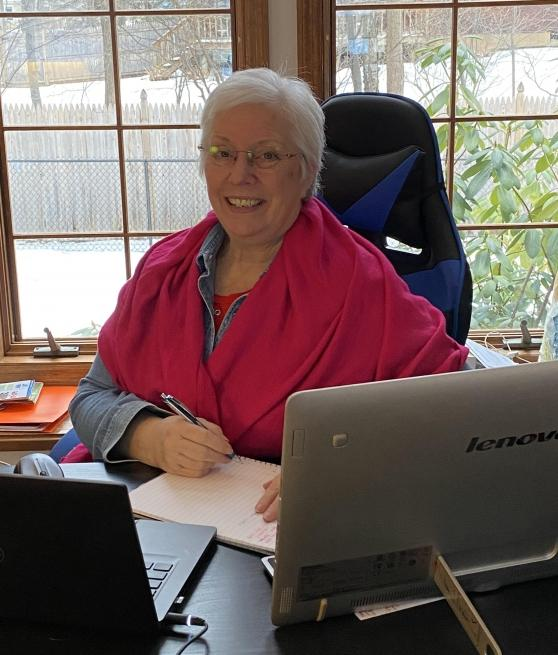 A woman with white hair and a pink shirt smiles while sitting at a desk.