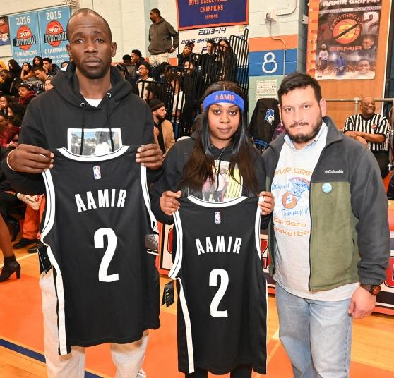 UFT Queens High Schools District Representative James Vasquez (right) with Aamir's parents, holding jerseys dedicated to Aamir by the Brooklyn Nets.