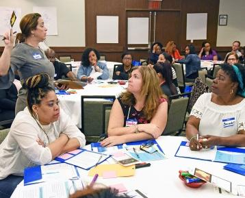 Laurie Hallick (standing) of the UFT Teacher Center leads the mathematics worksh